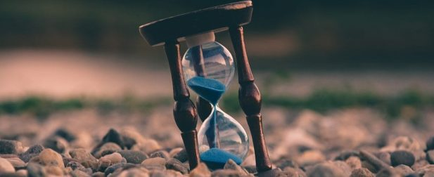 hourglass with blue sand on rocks