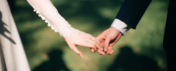 Wedding picture of bride and groom holding hands